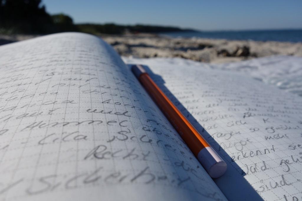 Notizbuch und Bleistift am Strand,