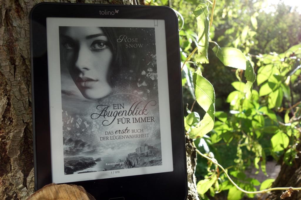 """Das Cover """"Ein Augenblick für immer - Das erste Buch der Lügenwahrheit"""" von Rose Snow fotografiert an einem Baumstamm"""