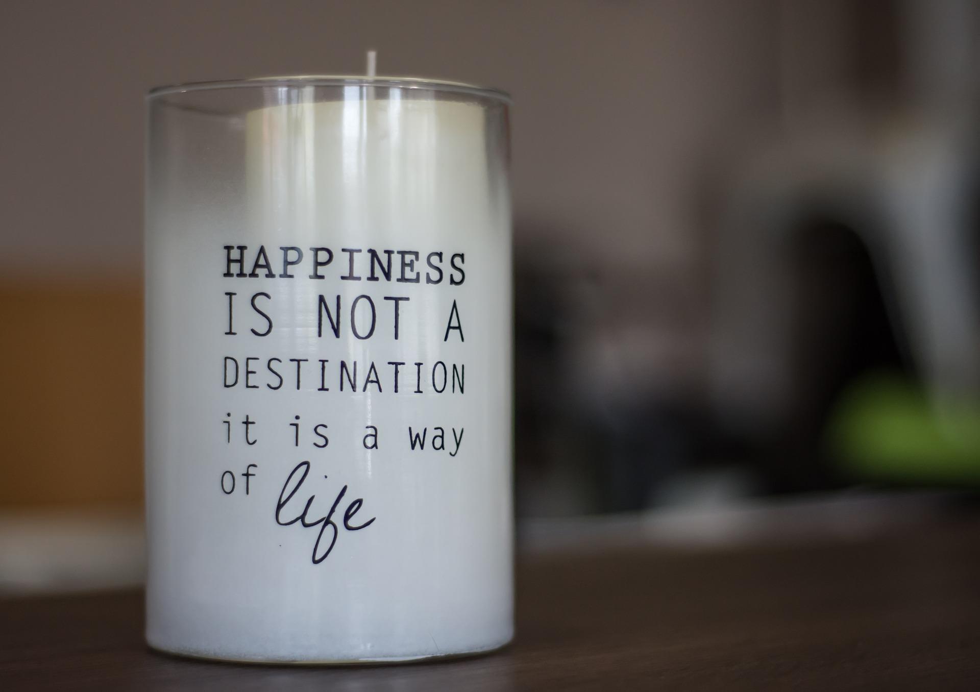 """Kerze mit der Aufschrift """"Happyness is not a destination it is a way of life"""" (Bild von Christo Anestev auf Pixabay)"""
