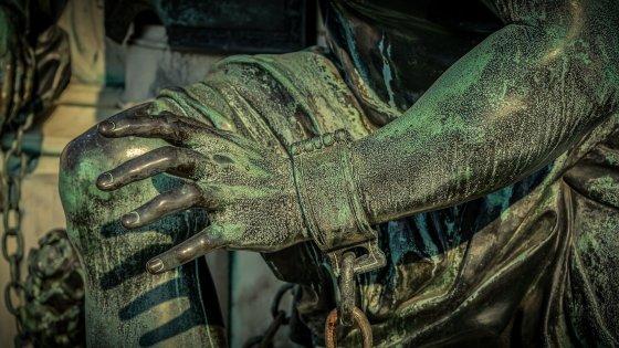 Detail einer Statue, das deren Hand mit Fessel und Eisenkette zeigt.