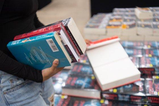 Eine Frau hält drei Bücher in der Hand, dahinter sieht man stapelweise Bücher (Bild von Ahmad Ardity auf Pixabay)